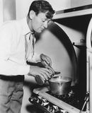 Man cooking on stove. (All persons depicted are no longer living and no estate exists. Supplier grants that there will be no model release issues Royalty Free Stock Photography