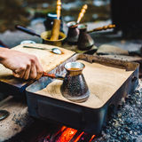 Man is cooking Turkish coffee in the box with sand under live coals Stock Photos