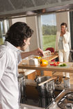 Man cooking woman with house model Stock Photos