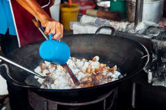 Man cooks at Kimberly Street Food Night Market. Man is cooking at Kimberly Street Food Night Market in George Town, Malaysia Stock Photo