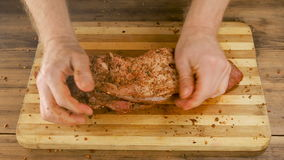 A man cooks meat on a cutting Board on the table from old wooden planks. Male hands sprinkle spices and crumple a piece stock footage