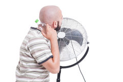 Man cooling down with blowing fan and cold water Royalty Free Stock Photography