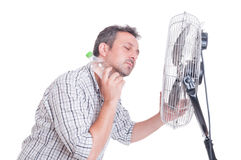 Man cooling down in front of blowing fan Stock Photography