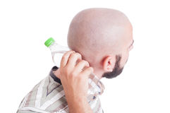 Man cooling his back neck with cold water bottle Stock Images