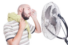 Man cooling his head with cold water bottle and fan Royalty Free Stock Images