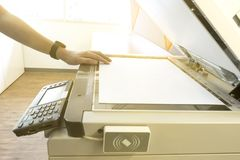 Man is copying document from a Photocopier with access control of scanning key card panel. A Man is copying document from a Photocopier with access control of stock photography