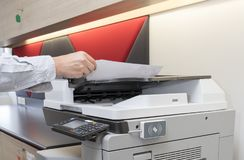 Man copying paper from Photocopier with access control for key card scanning stock images