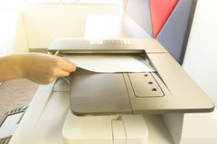 Man copying paper from Photocopier with access control for scanning key card sunlight from window.  Stock Photo