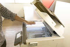 Man copying paper from Photocopier sunlight from window Stock Image