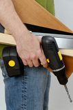 A man with a cordless screwdriver and wood in his hand in a green shirt Stock Image
