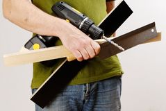 A man with a cordless screwdriver and wood in his hand in a green shirt Stock Images