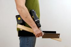 A man with a cordless screwdriver and wood in his hand in a green shirt Royalty Free Stock Image