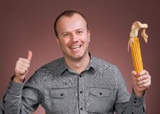 Man with corn. Young businessman holding corn cob in hand and showing yes sign on a brown background Stock Photos