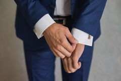 Man correct sleeves on shirt, hands close-up. Dressing, man's style Royalty Free Stock Image