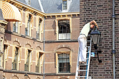 Man correcting lamp in front of building of dutch parliament - T Stock Image