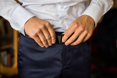 Man corrects belt, fees groom, man's hands, dressing, man wear pants, jeans Stock Images