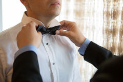Man corrects his friend bow tie. Man corrects his best friend bow tie Stock Image