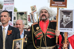 Man in Cossack military uniform holds portrait of relatives at Immortal regiment on 9 May, 2016 in Ulyanovsk, Russia stock photos