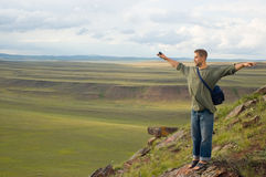 The man costs at mountain top. Having stretched hands royalty free stock photography