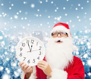 Man in costume of santa claus with clock Stock Photo