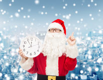 Man in costume of santa claus with clock Royalty Free Stock Image