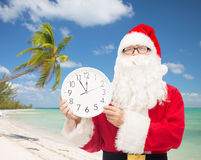 Man in costume of santa claus with clock Stock Images
