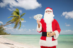 Man in costume of santa claus with dollar money Stock Photos