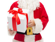 Man in costume of santa claus with gift box. Christmas, holidays and people concept - close up of santa claus with gift box Royalty Free Stock Photo