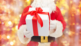 Man in costume of santa claus with gift box. Christmas, holidays and people concept - close up of santa claus with gift box over lights background Stock Photos