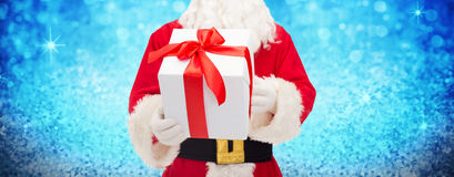 Man in costume of santa claus with gift box. Christmas, holidays and people concept - close up of santa claus with gift box over lights or blue glitter Stock Photos