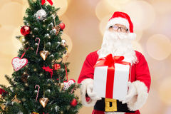 Man in costume of santa claus with gift box. Christmas, holidays and people concept - man in costume of santa claus with gift box and tree over beige lights Stock Images