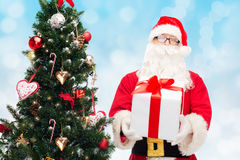 Man in costume of santa claus with gift box. Christmas, holidays and people concept - man in costume of santa claus with gift box and tree over blue lights Royalty Free Stock Photos