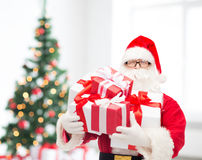 Man in costume of santa claus with gift boxes Royalty Free Stock Images