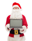 Man in costume of santa claus with laptop Stock Image