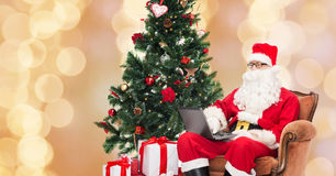 Man in costume of santa claus with laptop Stock Photography