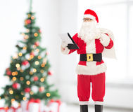 Man in costume of santa claus with notepad and bag Stock Photography