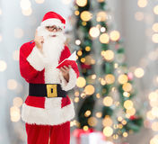 Man in costume of santa claus with notepad Royalty Free Stock Photos