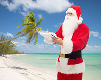 Man in costume of santa claus with notepad Stock Image