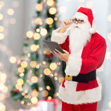 Man in costume of santa claus with tablet pc Stock Image