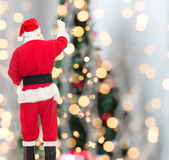 Man in costume of santa claus writing something. Christmas, holidays and people concept - man in costume of santa claus writing something from back over tree Stock Photo