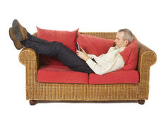 Man on a couch with an e-reader. Royalty Free Stock Image