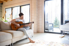 Man on couch with guitar Royalty Free Stock Photography