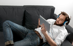 Man on the couch in headphone. Listen to music Stock Photo
