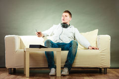 Man on couch with headphones smartphone and tablet Royalty Free Stock Photography