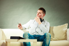Man on couch with headphones smartphone and tablet Royalty Free Stock Photo