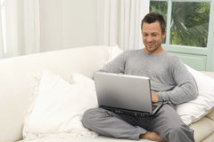 Man on couch with laptop at home. Royalty Free Stock Photos