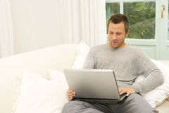 Man on couch with laptop at home. Stock Photos