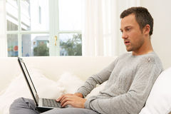Man on couch with laptop at home. Royalty Free Stock Photo