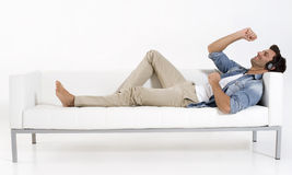 Man on the couch listening music Stock Images