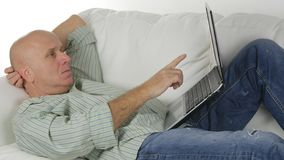 Man on a Couch Looking Worried to a Laptop Pointing with Finger royalty free stock image
